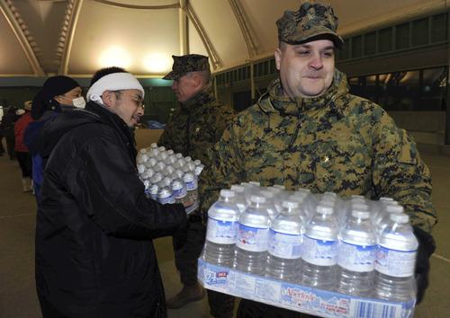 Masamine Kawaguchi, The Yomiuri Shimbun     The Associated Press A U.S. soldier volunteers to help victims Wednesday at a makeshift shelter in Rikuzentakata, northern Japan