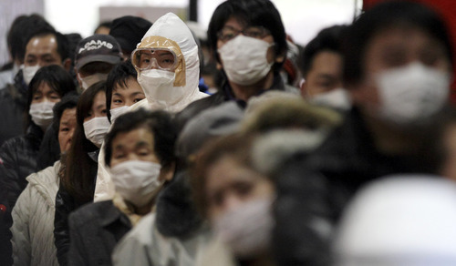 Gregory Bull   The Associated Press  An official in protective clothing stands with residents at they wait in a line to be scanned for radiation at a temporary scanning center for residents living close to the quake-damaged Fukushima Dai-ichi nuclear power plant Wednesday, March 16, 2011, in Koriyama, Fukushima Prefecture, Japan.
