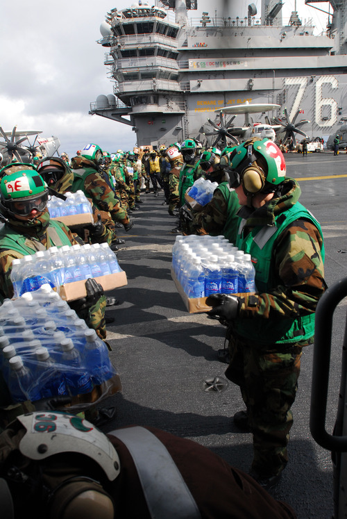 In this image provided by the U.S. Navy sailors load bottled water on a Sea Hawk helicopter assigned to the Black Knights of Helicopter Anti-Submarine Squadron 4 aboard the aircraft carrier USS Ronald Reagan Tuesday March 15, 2011. Ronald Reagan is off the coast of Japan providing humanitarian assistance to Japan. (AP Photo/US Navy - Dylan McCord)