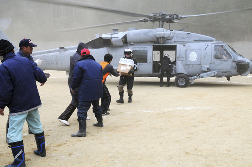 In this March 15, 2011 photo released by US Navy, Naval Air Crewman 2nd Class Zack DelCorte, holding boxes, assigned to the Black Knights of Helicopter Anti-Submarine Squadron (HS) 4, currently embarked with the aircraft carrier USS Ronald Reagan (CVN 76), hands bottled water to a Japanese citizen at a northeastern coastal city of Japan  affected by Friday's tsunami.  Ships and aircraft from the Ronald Reagan Strike Group are conducting Search and Rescue (SAR) operations and resupply missions throughout northern Japan's affected areas in support of Operation Tomodachi which means