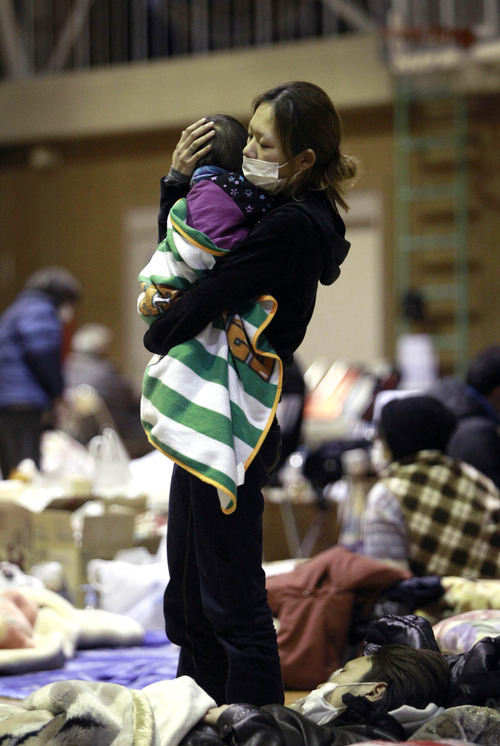 Wally Santana     The Associated Press A woman holds her child Wednesday at a shelter after being evacuated from areas around the Fukushima nuclear facilities damaged by last week's major earthquake and following tsunami  in Fukushima city, Fukushima prefecture, Japan.