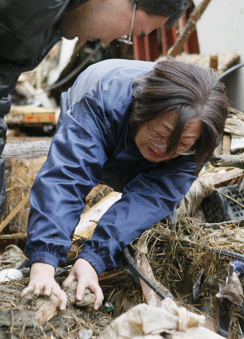 Kyodo News Yoshie Murakami cries as she holds a hand of her dead mother Wednesday in the rubble near the spot where her home used to be  in Rikuzentakata, Iwate Prefecture. Murakami's 23-year-old daughter is still missing, Kyodo said.