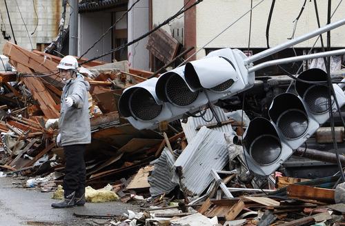 Shizuo Kambayashi     The Associated Press A construction laborer controls the traffic Wednesday at a devastated area in Kesennuma, Miyagi Prefecture, northern Japan.
