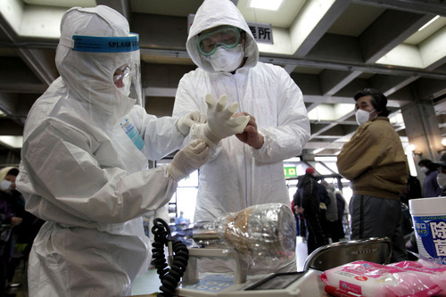 Officials put on protective clothing at a temporary scanning center for residents living close to the quake-damaged Fukushima Dai-ichi nuclear power plant Wednesday, March 16, 2011, in Koriyama, Fukushima Prefecture, Japan. (AP Photo/Gregory Bull)