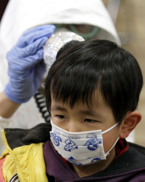 A boy is scanned for radiation at a temporary scanning center for residents living close to the quake-damaged Fukushima Dai-ichi nuclear power plant Wednesday, March 16, 2011, in Koriyama, Fukushima Prefecture, Japan. (AP Photo/Gregory Bull)