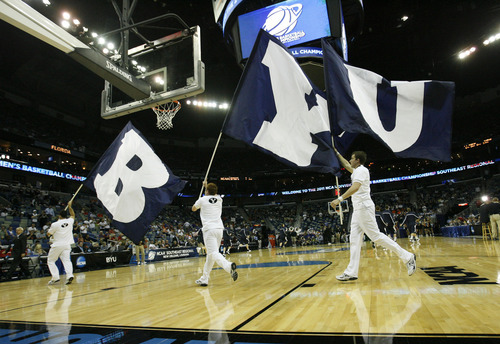 Scott Sommerdorf  |  The Salt Lake Tribune The BYU flag bearers run around prior to tip-off. BYU lost 83-74 in OT to Florida at the New Orleans Arena in their first round game of the