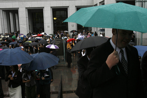 Conference-goers walk out into the rain after a past Saturday session of the LDS General Conference.  Tribune file photo