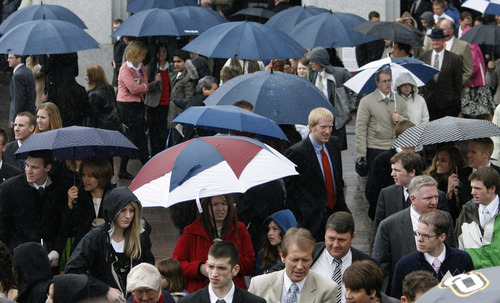 LDS faithful brave the rain and cold temperaturess, between sessions of the 179th annual General Conference at the LDS Conference Center in 2009. Tribune file photo