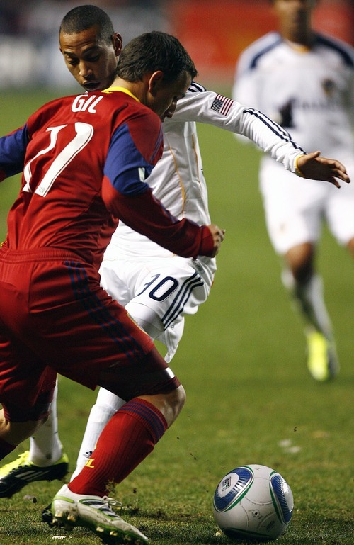 Djamila Grossman     The Salt Lake Tribune  Real Salt Lake's Luis Gil (21) defends the ball against Los Angeles Galaxy's Paolo Cardozo (30) during the second half of a game at Rio Tinto Stadium in Sandy, Utah, on Saturday,  March 26, 2011. RSL won the game.