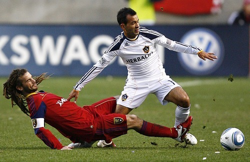 Djamila Grossman     The Salt Lake Tribune  Real Salt Lake's Kyle Beckerman (5), falls as he tries to kick the ball away from Los Angeles Galaxy's Juninho (19) during the first half of a game at Rio Tinto Stadium in Sandy, Utah, on Saturday,  March 26, 2011. RSL won the game.
