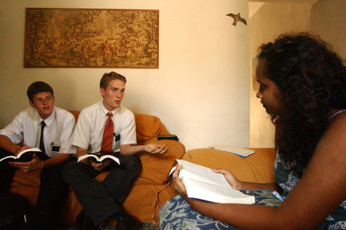 Elder Melo, left, and Elder Timothy teach a lesson in 2002 to Magda De Souza in her parent's home in Bangu, Rio de Janeiro, Brazil. Tribune file photo