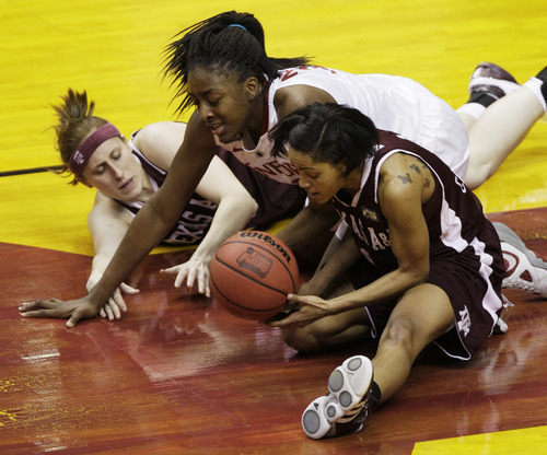 Texas A&M players Kelsey Assarian, left, and Sydney Carter, right, fight for a loose ball with Stanford's Nnemkadi Ogwumike (in the first half of a women's NCAA Final Four semifinal college basketball game in Indianapolis, Sunday, April 3, 2011.(AP Photo/Amy Sancetta)