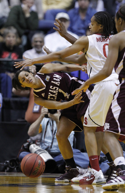 Texas A&M's Sydney Carter (4) makes a pass while being defended by Stanford's Melanie Murphy (0) in the first half of a women's NCAA Final Four semifinal college basketball game in Indianapolis, Sunday, April 3, 2011. (AP Photo/Michael Conroy)