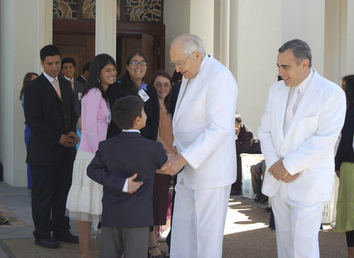 LDS apostle L. Tom Perry, center, who oversees the church in South America ,and Area President Francisco Vinas, right, in their temple whites greet young Chilean member after a dedication. Tribune file photo