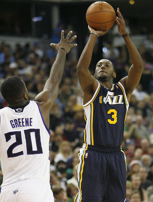 Utah Jazz guard Kyle Weaver, right, shoots over Sacramento Kings defender Donte Greene during the first half of an NBA basketball game in Sacramento, Calif., Sunday, April 3, 2011. (AP Photo/Steve Yeater)