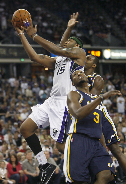 Sacramento Kings center DeMarcus Cousins (15) drives to the basket against Utah Jazz defender Kyle Weaver, front, and another Jazz player during the second half of an NBA basketball game in Sacramento, Calif., Sunday, April 3, 2011. The Kings won 106-97. (AP Photo/Steve Yeater)