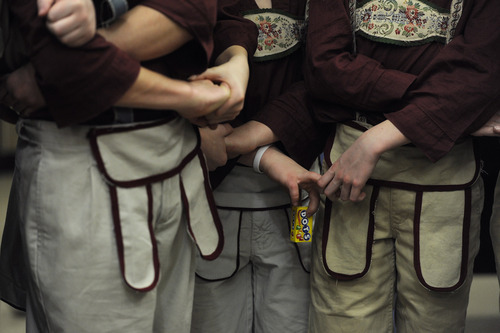 Sarah A. Miller  |  The Salt Lake Tribune  A group of boys playing lonely goatherds hold hands, and candy, during the moment of silence before their performance of