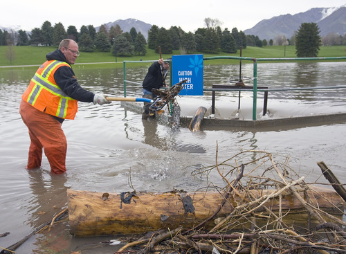 Al Hartmann   |  The Salt Lake Tribune  Bob Deegan, left, and Kelly Brown with the Salt Lake City Public Utilities Storm Water Department clear debris at the headwall grate at the south end of Sugarhouse Park on Wednesday, April 20.   Mountain Dell Reservoir had to release water down Parley's Creek, kicking up debris along the way.  This is a routine job to keep the water flowing.