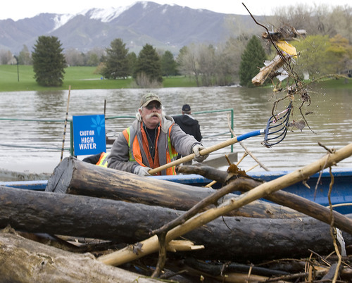 Al Hartmann   |  The Salt Lake Tribune  Brent Sainsbury, with Salt Lake City Public Utilities Storm Water Deptartment, throws wood and debris into truck that was collected from a  headwall grate at the west end of Sugarhouse Park on Wednesday, April 20.  Mountain Dell Reservoir had to release water down Parley's Creek, kicking up debris along the way.  This is a routine job to keep the water flowing.