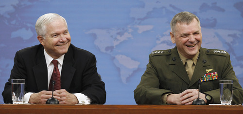 Defense Secretary Robert Gates, left, and Joint Chiefs Vice Chairman Gen. James Cartwright react to a very long question from a journalist during a media availability at the Pentagon, Thursday, April 21, 2011. (AP Photo/Alex Brandon)