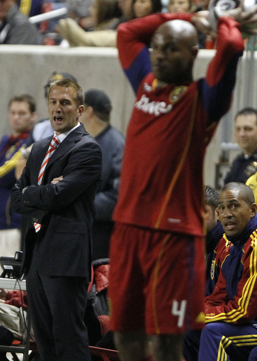 Real Salt Lake coach Jason Kreis, left, calls out to his team as Real Salt Lake's Jamison Olave throws in the ball during the first half of an MLS soccer Western Conference semifinal on Saturday, Nov. 6, 2010, in Sandy. (AP Photo/Jim Urquhart)