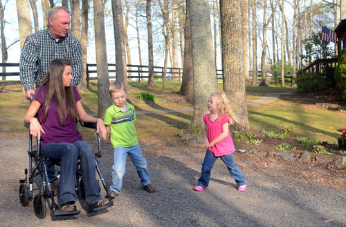 Kristen E. Conway  |  for The Salt Lake Tribune Megan Cate's husband Joe pushes her down the driveway of their Culpeper County, Va., home with their children DJ, 6, and Valeen, 4.  Megan Cate is unable to walk for extended distances and uses the chair on outings with the family.