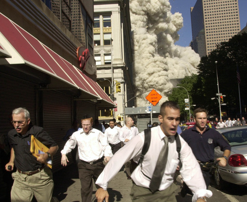 People run from the collapse of one of the twin towers of New York's World Trade Center in this Sept. 11, 2001,  file photo. (AP Photo/FILE/Suzanne Plunkett)