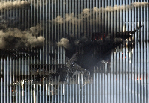 The north tower of New York's World Trade Center shows the impact left by a hijacked Boeing 767, American Airlines Flight 11, in this Sept. 11, 2001, file photo. A person is just visible, standing at the bottom of the gaping hole.  (AP Photo/Amy Sancetta/FILE)