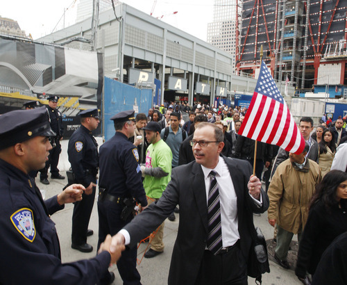 A commuter holds an American flag while shaking hands with a police officer at the World Trade Center site in New York on Monday, May 2, 2011. Under construction, the Freedom Tower is seen at top right. (AP Photo/Mark Lennihan)