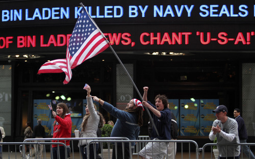 Melissa LaCour, left, Brittany McGarry, second from left, Bryan Murray, second from right, and Dennis Vincent celebrate outside the ABC studio in New York's Times Square as news of Osama bin Laden's death is announced on the ticker,  Monday, May 2, 2011.  (AP Photo/Mary Altaffer)