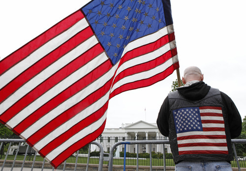 Dan Parker from Shamokin, Pennsylvania, stands outside the White House with a U.S. flag in Washington, D.C., U.S., on Monday, May 2, 2011. Al-Qaeda leader Osama bin Laden, the architect of a radical Islamist movement that killed almost 3,000 people on Sept. 11, 2001 and recast global security and politics, was killed in Pakistan yesterday after a decade on the run in a firefight with a team of U.S. operatives who raided the compound where he had been hiding. Rich Clement/Bloomberg