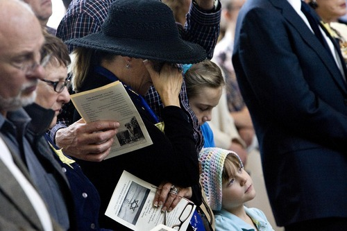 Djamila Grossman     The Salt Lake Tribune  Wanita Panza of Midway gets emotional as she stands with her husband Chuck and daughters Aili, 5, and Eliyah, 11, during the memorial prayer at a Holocaust Memorial Commemoration at the Capitol Rotunda in Salt Lake City, Utah, on Sunday, May 1, 2011.
