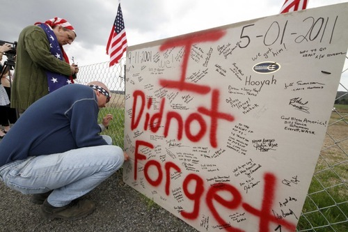 Jeff Ray, right, and Jan Ray of Shanksville, Pa., attach a sign to the fence overlooking the crash site of  United Flight 93 in Shanksville, Pa., Monday, May 2, 2011. Osama Bin Laden, the face of global terrorism and mastermind of the Sept. 11, 2001, attacks, was tracked down and shot to death Monday in Pakistan by an elite team of U.S. forces, ending an unrelenting manhunt that spanned a frustrating decade. (AP Photo/Gene J. Puskar)