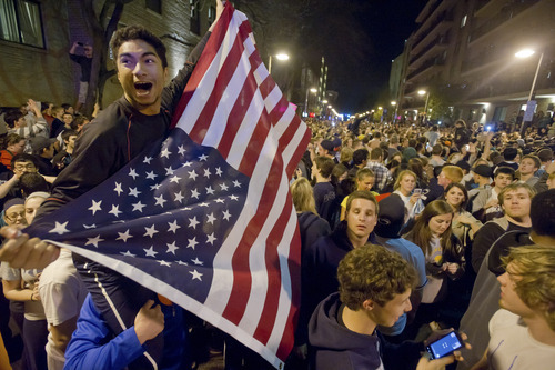 Penn State senior Jake Librizzi holds an American flag as he and others fill Beaver Canyon Avenue in downtown State College, Pa., shortly after learning about the death of Osama bin Laden, the mastermind behind the Sept. 11, 2001 terrorist attacks. (AP Photo/Andy Colwell)