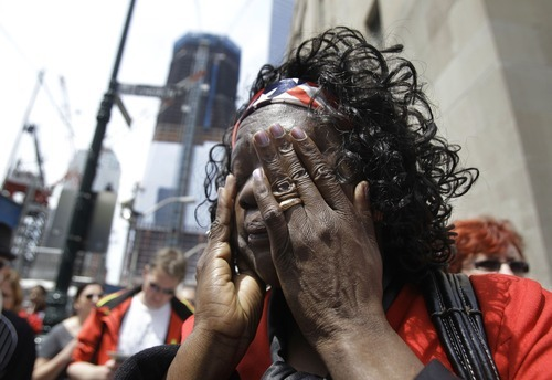 Sudanese immigrant Laija Elioba, of New York, wipes away tears after placing patriotic balloons at an impromptu memorial at ground zero in New York, Tuesday, May 3, 2011.  Elioba, who lived in New York on 9-11, but has never visited the World Trade Center site until now, said she was moved to pay tribute Tuesday after the death of Osama bin Laden. (AP Photo/Kathy Willens)
