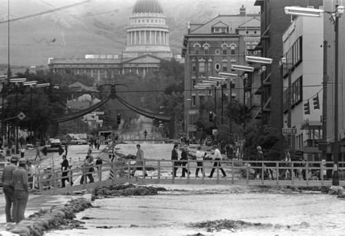 Al Hartmann | The Salt Lake Tribune  Life went on for downtown pedestrians and workers after construction crews quickly built footbridges over the State Street river in late May 1983 after City Creek had to be diverted down the road.