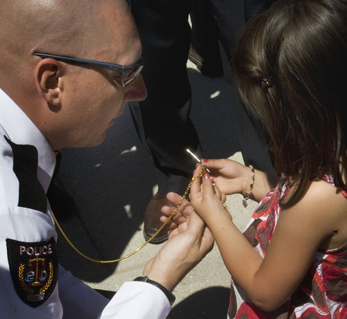 Steve Griffin  |  The Salt Lake Tribune  Macee Yazzie holds the hand cuff key that belonged to her father,  Joshua, a Bureau of Indian Affairs Officer, and is now carried by Roosevelt police officer Mark Cornaby. They were part of a memorial on the Capitol grounds  in Salt Lake City on Thursday, May 5, 2011. Officer Yazzie, 33, died in 2010 after his car went over a 200-foot embankment near Bottle Hollow Reservoir on the Ute Indian Reservation in Uintah County. Cornaby was a life-long friend of Yazzie and carries the key in memory of his friend.