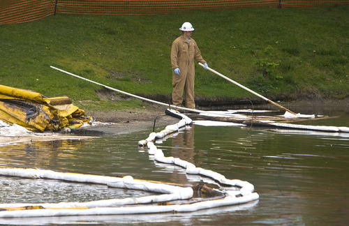 Al Hartmann  | The Salt Lake Tribune A worker skims water for oil on Liberty Park Pond from the pipline break in the days after the spill last summer.   Absorbent-lined booms contained the oil on the surface of the water.