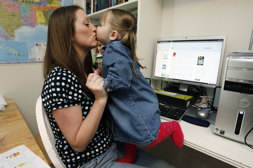 Francisco Kjolseth  |  The Salt Lake Tribune Blogger Cindi Braby, mother of five, from Eagle Mountain gets a kiss from her daughter Mary, 2, on Thursday, May 5, 2011, at the computer where she does much of her work as author of Utah Mom's Life. She blogs about her marriage, her children and life in Utah.