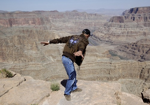 Swiss adventurer Yves Rossy pretends to leap into the Grand Canyon from Guano Point on the Hualapai Indian Reservation Friday, May 6, 2011. Rossy canceled first US flight in a custom built jet suit due to safety concerns.  The Federal Aviation Administration earlier Friday had approved plans for the 51-year-old adventurer to use the Grand Canyon as a backdrop for his first U.S. flight in a jet-propelled wing suit.  Rossy calls himself the JetMan.   (AP Photo/Matt York)