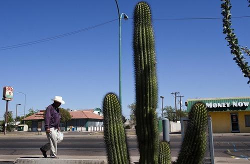DJAMILA GROSSMAN  |  Ahora Utah -- Un señor camina por la East Main Street de Mesa, Arizona. Al fondo se observa un restaurante de comida mexicana que fue forzado a cerrar y un negocio de avances de dinero que apenas se mantiene a flote. En este suburbio de Phoenix varios negocios cerraron y muchos habitantes abandonaron sus hogares, un hecho que algunos dicen fue originado por la ley de inmigración SB1070.