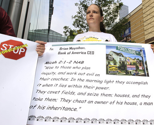 Chuck Burton  |  The Associated Press Erin Blackmon, of Albemarle, N.C., holds a sign protesting Bank of America's foreclosure practices Wednesday.
