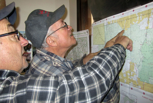 Mel Basanez, left, and Bill Landon, look at a map of the northeastern Nevada wilderness on Tuesday, May 10, 2011 in Mountain City, Nev.  Efforts to find 59-year-old Albert Chretien were suspended Tuesday by rain, low clouds and flood warnings in a remote corner of Elko County, Nev., where Chretien and his wife became stranded along a muddy road on a trip to Las Vegas.  Rita Chretien continues to recover after being rescued Friday by a group of hunters.   The couple from Penticton, British Columbia, is believed to have turned off a highway and onto a northeastern Nevada mountain road looking for a shortcut to Jackpot, Nev., a stop on their way to a Las Vegas trade show. When their van became stuck in the mud, Albert Chretien set out on his own with a GPS, hoping to walk more than 20 miles to the town of Mountain City. He never returned. (AP Photo/Brian Skoloff)