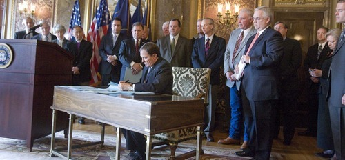 Paul Fraughton  |  The Salt Lake Tribune  With religious, community, business and government leaders behind him, Utah Gov. Gary Herbert on Tuesday signed into law immigration  bills passed in this year's legislative session, including a controversial guest-worker program (HB116) and an enforcement bill (HB497).