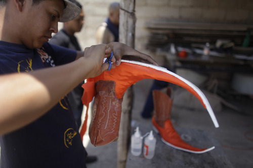 In this picture taken Saturday, May 7, 2011, young men create their own pointy boots that they will use at a dance competition at night in Matehuala, Mexico.  The dance crews were the first to embrace the flashy pointy boot-craze that has swept through the Mexican town of Matehuala, spread to nearby cities and even taken by migrants across the border into the United States. (AP Photo/Dario Lopez-Mills)