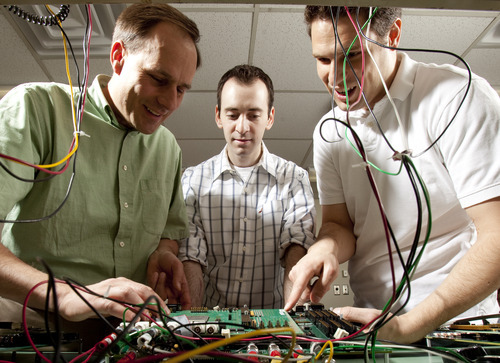BYU Associate Professor Michael Wirthlin helps graduate students Patrick Ostler and Nathan Rollins work on a circuit board that was launched to the International Space Station in Endeavour Monday morning. Photo courtesy Brigham Young University.