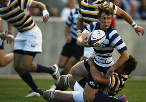 Djamila Grossman     The Salt Lake Tribune  Brigham Young University Dylan Lubbe (10) passes on the ball as he gets tackled by the University of California's Ryan Hodson (5) in the National College Rugby Championship game at Rio Tinto Stadium in Sandy, Utah, on Saturday, May 21, 2011. BYU lost.