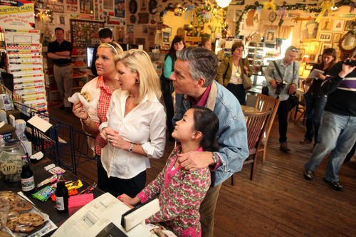 Max Bittle, special to The Salt Lake Tribune Former Utah Gov. Jon Huntsman Jr. looks at old political posters on the wall at Robie's Country Store in Hooksett, N.H., on Saturday. With him are wife Mary Kaye and daughters Elizabeth and Gracie Mei.