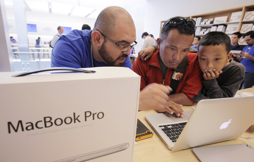 Passang Sherpa, center, and his son, Kalsang Dorji Sherpa, 11, right, receive help with their new 13-inch Apple MacBook Pro from Apple worker Doug Rodriguez, left, as part of Apple's new