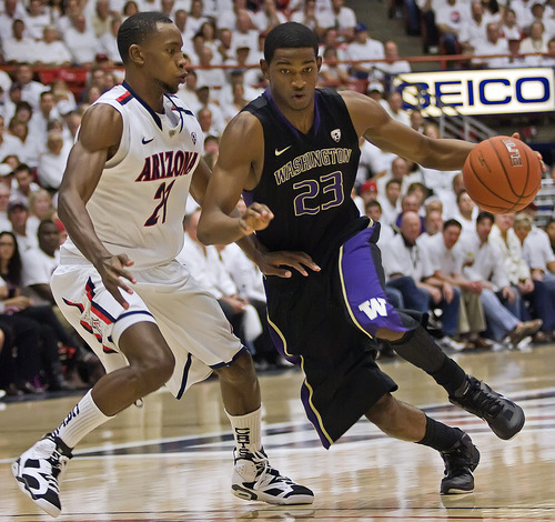 Wily Low     The Associated Press Washington's C.J. Wilcox (23) dribbles around Arizona's Kyle Fogg (21) in the first half of an NCAA college basketball game at McKale Center in Tucson, Ariz., Feb. 19, 2011.